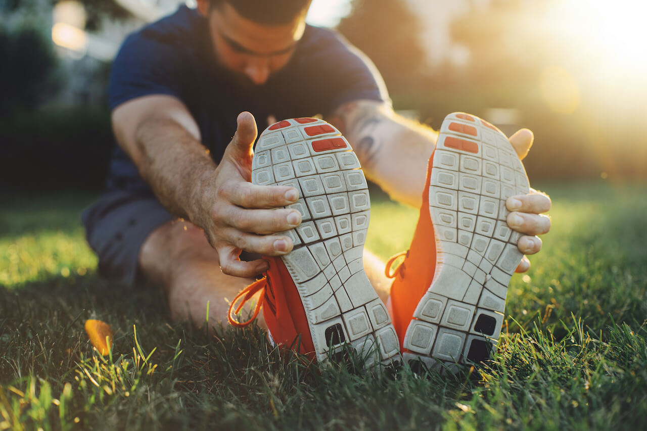 Attractive young man stretching in the park before running at the sunset focus on shoes